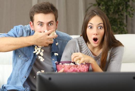 Un homme et une femme mange du popcorn