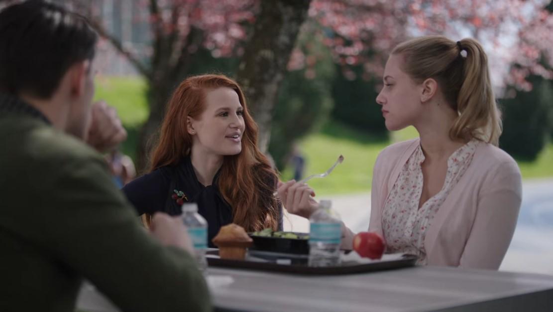 Kevin (Casey Cott) de dos au premier plan. Cheryl (Madelaine Petsch) et Betty (Lili Reinhart) assis à une table de Riverdale High. Les couleurs rouge et vert sont en opposition sur ce plan.