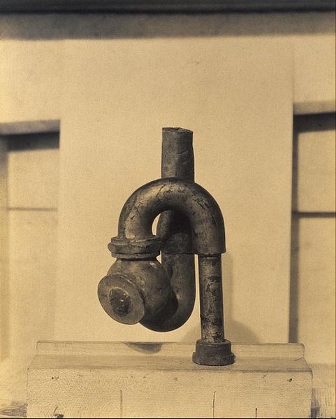 """La sculpture """"God"""" de Elsa von Freytag-Loringhoven et Morton Schamber fait écho à """"La Fontaine"""" par l'utilisation du tuyau de plomb."""